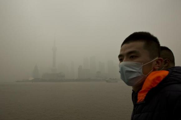 A man wears a face mask while walking on the Bund in front of the financial district of Pudong during a hazy day in downtown Shanghai December 9, 2013.