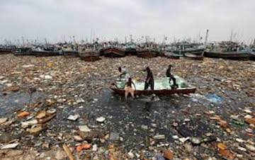 Boys collect recyclable items from polluted waters in front of fishing boats at Fish Harbor in Karachi, Pakistan, August 17, 2016. REUTERS/Akhtar Soomro